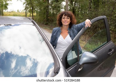 Woman standing next to car smiling at the camera