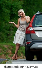 woman standing next to her car and talking to mobile phone
