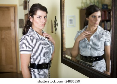 Woman standing next to mirror inside a home