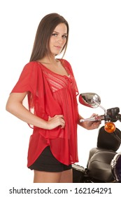 A woman is standing next to a motorcycle and is wearing a red shirt.