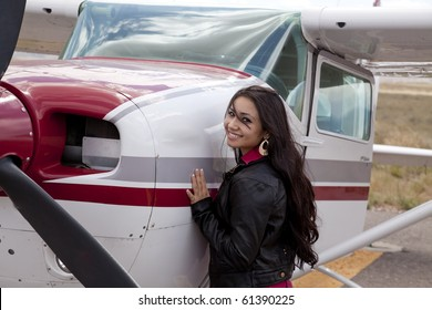 A woman standing next to a small airplane.