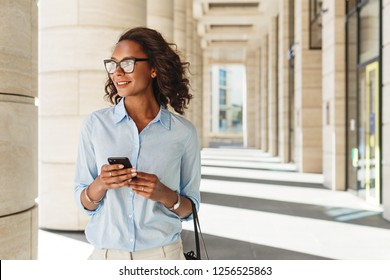 Woman standing at office building. Business person with mobile phone outdoors looking away.