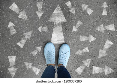 Woman standing on asphalt road with arrows pointing in different directions. Concept of choice