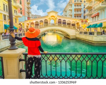 Woman standing on balcony looking famous bridge of Venice, Doha Qatar, at twilight. Caucasian tourist at Qanat Quartier in the Pearl-Qatar, Persian Gulf, Middle East. Travel in Arabian Peninsula.