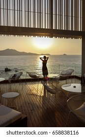 Woman standing on the balcony watching beautiful aegean sea view.Aegean sea view from apartment suite or hotel room.Holiday and relaxation concept.Leisure and tranquility
