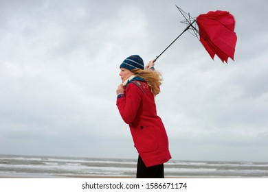 A woman standing on a beach with her umbrella blowing inside out