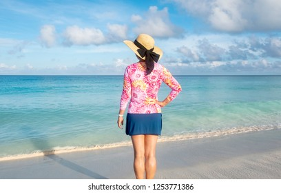 Woman Standing on a Caribbean Beach with a Short Skirt, Colorful Top and Straw Hat