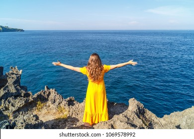 Woman standing on a cliff in yellow dress with open arms looking into the horizon. Broken Beach, Nusa Penida, Indonesia