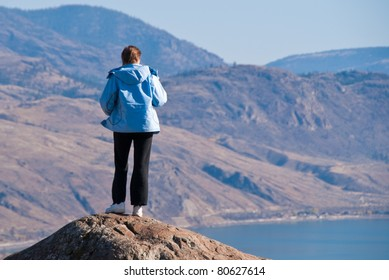 A woman standing on cliff's edge over a fantastic mountain view