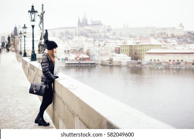 Woman standing on edge of bridge, leaning on brick railing. She is dressed in black winter clothing and hat with black handbag on her shoulder and gray scarf around his neck. Background out of focus.