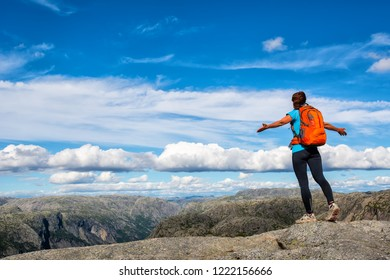A woman is standing on the edge of cliff on the way to boulder (Kjeragbolten) stuck in between the mountain crevices of Kjerag above Lysefjord, near Lysebotn, Norway. The feeling of complete freedom