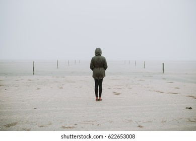 Woman standing on the empty beach