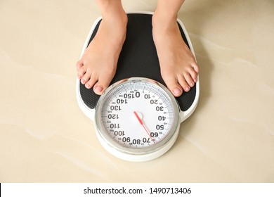 Woman standing on floor scales indoors, above view. Overweight problem