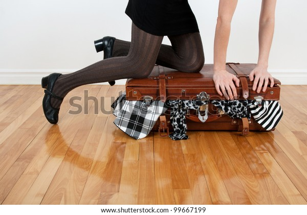 Woman standing on her knees on an overfilled suitcase with clothing.