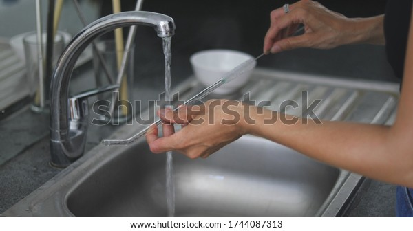 woman standing on kitchen and washing reusable glass straw. Zero waste concept