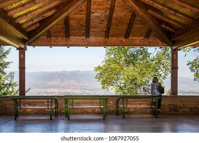 Woman standing on a large wooden balcony overlooking Skopje Macedonia.