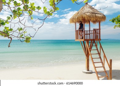 Woman standing on lifeguard tower on the sand beach in Cambodia