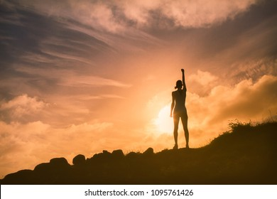 Woman standing on a mountain with fist in the air. People courage and feeling confident.