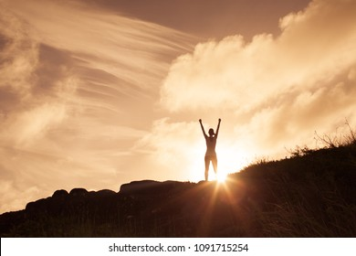 Woman standing on a mountain top with arms in the air celebrating. Victory and winning concept.