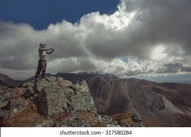 woman standing on mountain top and makes photo on  cell phone