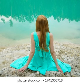 Woman standing on near the scenic calm lake with her hand raised. beauty, fashion photo with mirror effect.Young girl wear long blue dress, sitting alone near the lake. Weekend outdoors. Back view