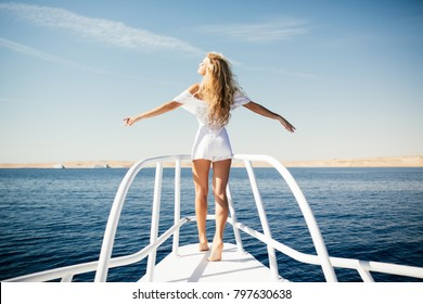 Woman standing on the nose of the yacht at a sunny summer day, breeze developing hair, beautiful sea on background