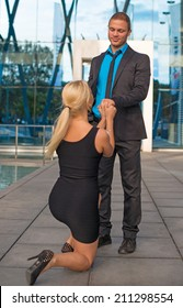 Woman standing on one knee and making proposal to man.