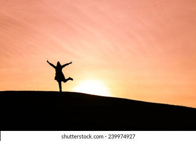 Woman standing on one leg against a setting sun