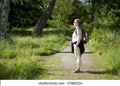 Woman standing on a path enjoying the forest in evening light