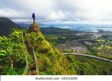 Woman standing on the peak of a mountain overlooking a town below. A bay in the distance. A stairway continues up the mountain. Taken on the Haiku Stairway to Heaven in Hawaii.
