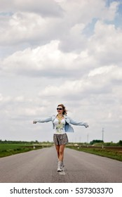 Woman standing on the road with arms spread