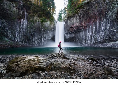 A woman standing on the rock at Abiqua Falls, Oregon. Abiqua Falls is one of the hidden gems in Oregon. Oregon also has many unrecognized falls.  Oregon also has the landscape of old volcanic rocks