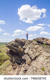Woman standing on a rock against a blue sky