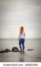 Woman standing on a rock and looking to the sea