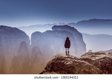 Woman standing on a rock at Meteora in Greece watching the view.