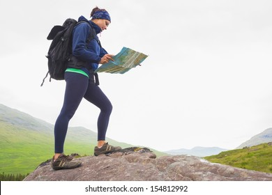 Woman standing on a rock reading map on hike in the countryside