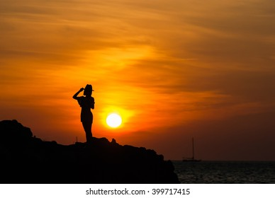 Woman standing on rock in sea and looking to a sun