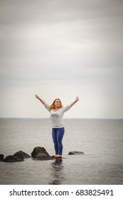 Woman standing on a rock to the sea with arms up