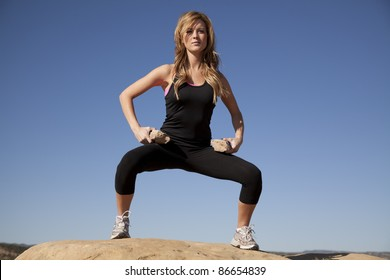 a woman standing on a rock in squat position with a serious expression holding her rocks like weights on her thighs.