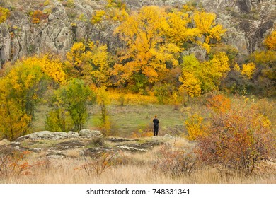 Woman standing on the rock surrounded by autumn colored trees, beautiful fall season outdoor theme