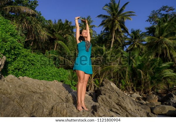 a woman standing on the rocks, against the jungle stretches his hands in the sky .closing your eyes from the pleasure of rest ,