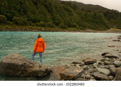 Woman standing on rocky river shoreline on south island of New Zealand. Whataroa River.