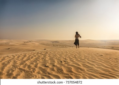Woman standing on a sand dune in the desert of Qatar