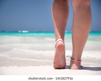 Woman standing on sandy beach with turquoise sea water. Female legs walk into the sea with waves. Travel destinations. Summer holidays