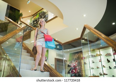 Woman standing on the stairs of clothes store looking down