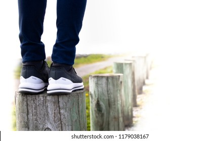 A woman standing on stump next to the road. Concept of living life with confidence and carefulness every steps of moving forward to make sure life safe. Free copyspace for text on right.