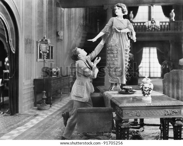 Woman standing on a table being adored by a man