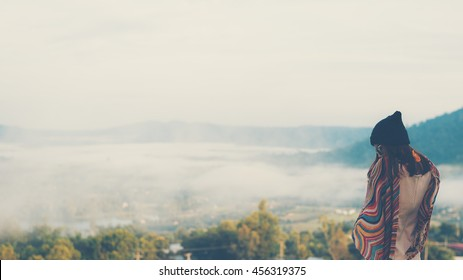 woman is standing on the top of foggy mountain
