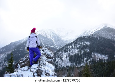 Woman standing on the top of the high Tatra mountains. Hiker on the peak. Recreation on the free time in the winter. Sport concept, fit girl in winter outdoors clothes.