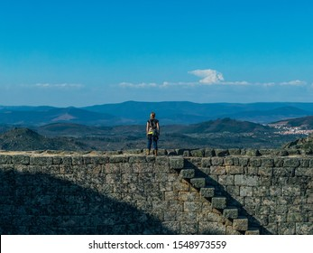 Woman standing on top of Monsanto's hilltop castle wall. Looking out over the view of mountains, villages and plains of Portugal and Spain.